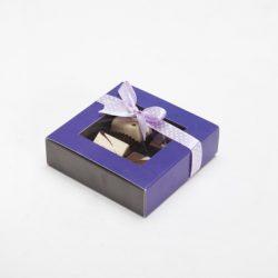 קופסה קטנה סגולה מרובעת עם חלון וסרט ורוד עם נקודות לבנות